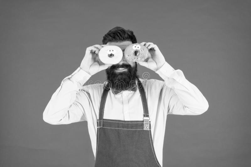 Having fun with donut. funny hipster cook doughnut. temptation while diet. male cooking bakery. bearded man chef. brutal. Waiter on kitchen. mature man red stock image