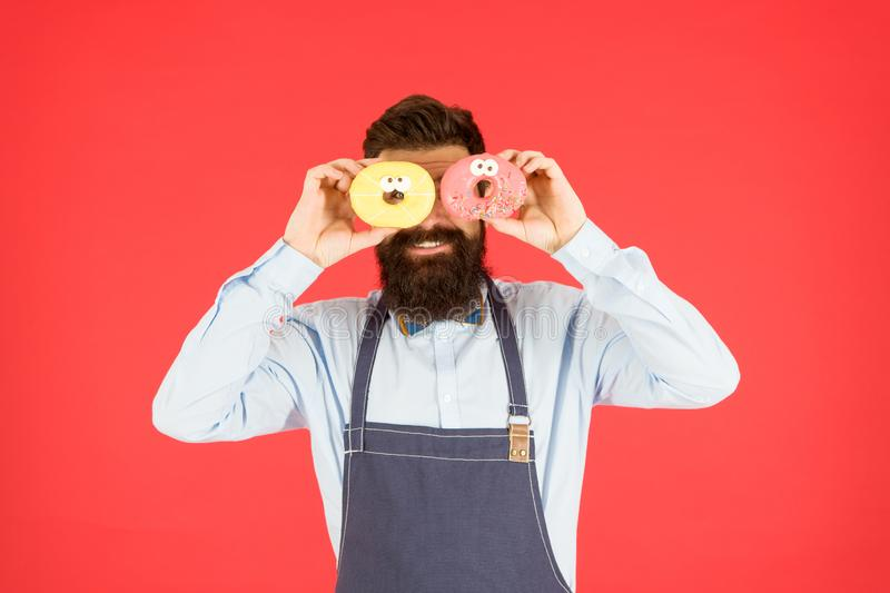 Having fun with donut. funny hipster cook doughnut. temptation while diet. male cooking bakery. bearded man chef. brutal. Waiter on kitchen. mature man red royalty free stock images