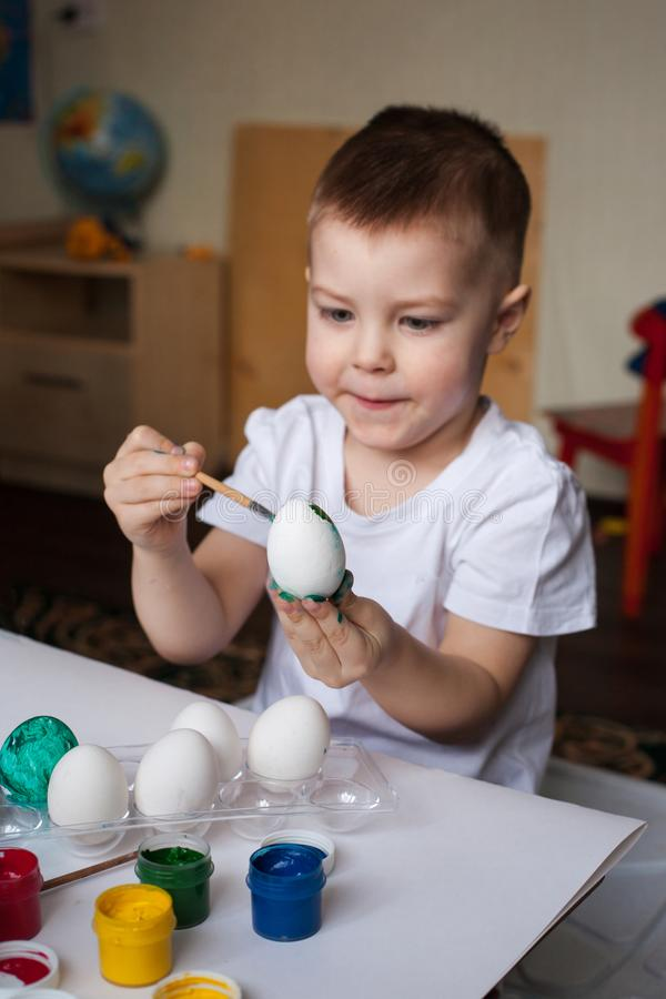 Having fun on Easter egg hunt. Children with colorful eggs in basket. Toddler kid boy play indoor, selective focus. royalty free stock images