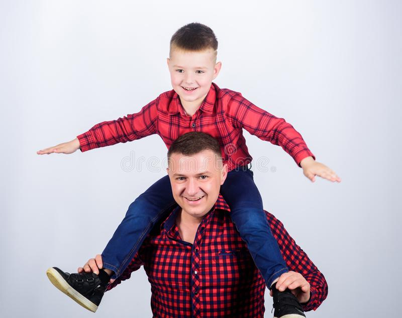 Having fun. Fathers day. Father example of noble human. Family time. Best friends. Father little son red shirts family. Look outfit. Child riding on dads royalty free stock image