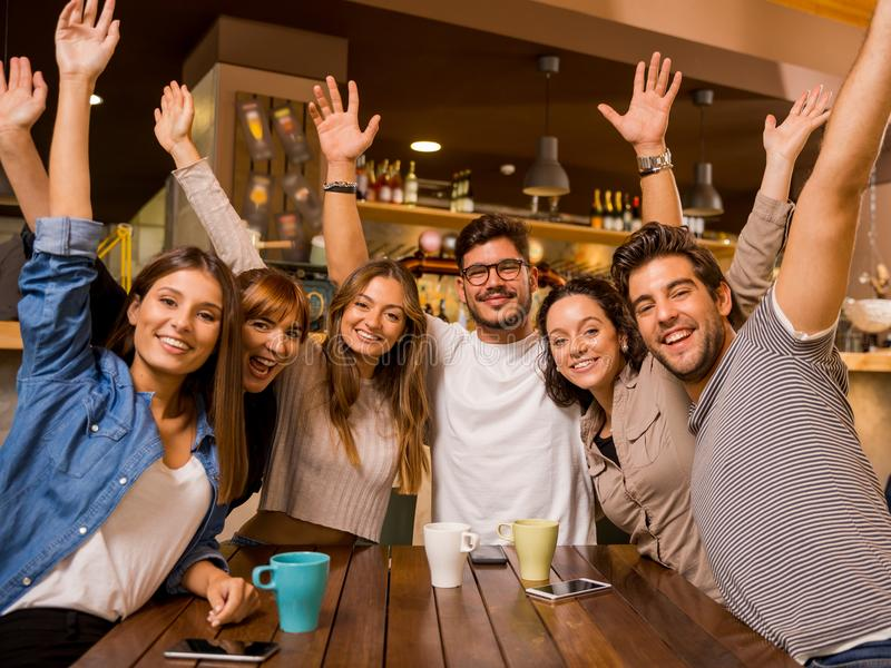 Having fun. Group of friends raising hands and looking to the camera stock photo