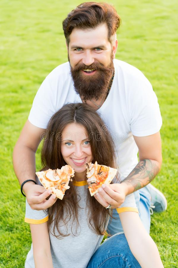 Having fun. happy couple eating pizza. Healthy food. summer picnic on green grass. Diet. hunger. family weekend. couple stock photo