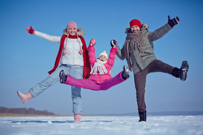 Having fun. Joyful family of father, mother and daughter in winterwear royalty free stock photos