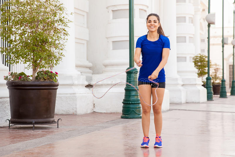 Having fun with a jump rope. Cute Latin woman working out in the city and having fun with a jump rope stock photo