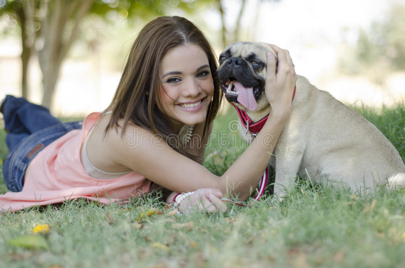 Having fun with my dog. Young beautiful woman having fun and spending some time with her pug dog at a park royalty free stock photo
