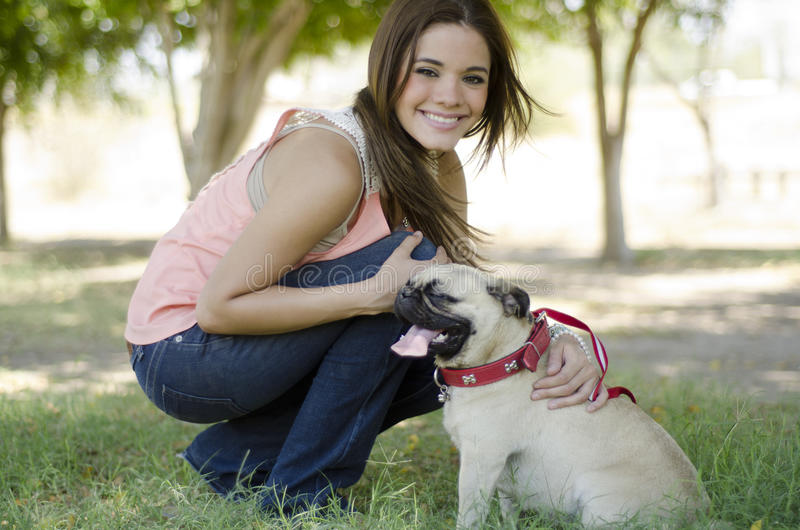 Having fun with my dog. Young beautiful woman having fun and spending some time with her pug dog at a park stock photography