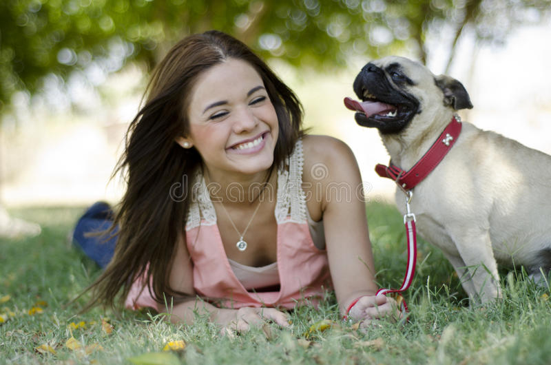 Having fun with my dog. Young beautiful woman smiling and having fun with her pug dog at a park stock photos