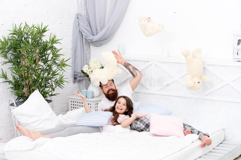 Having fun pajamas party. Slumber party. Happy fatherhood. Ending of crazy evening. Dad and girl relaxing bedroom stock photo