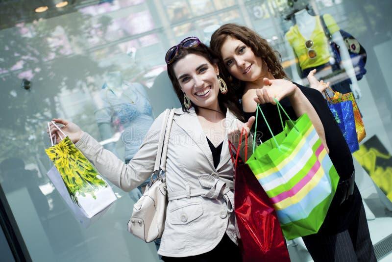 Having fun shopping. Women friends having funshopping downtown royalty free stock photo