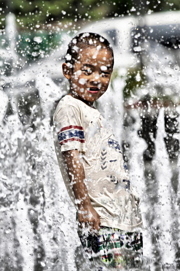 Having fun in summer fountain. Chinese little boy playing fountain on square in hot summer royalty free stock image