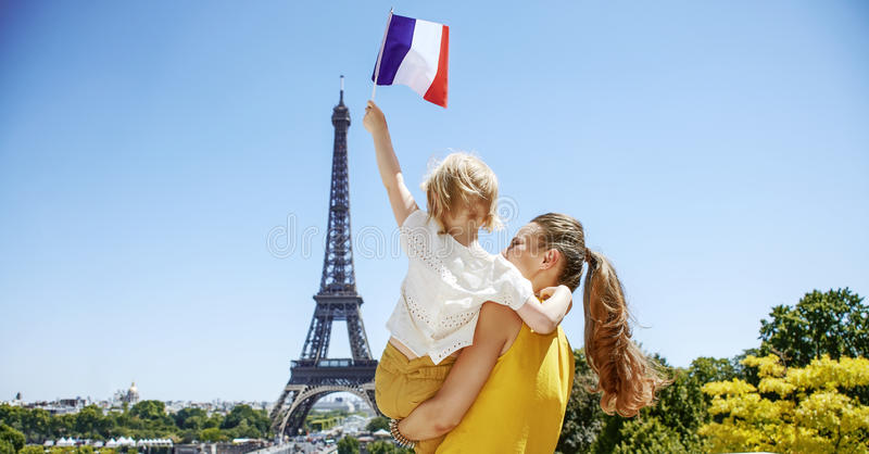 Mother and child travellers rising flag in Paris, France. Having fun time near the world famous landmark in Paris. Seen from behind mother and child travellers stock image