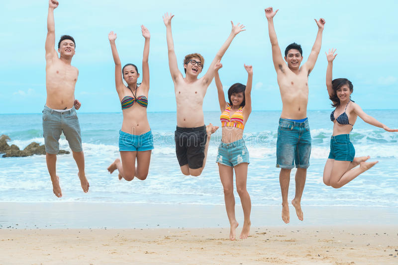Having fun together. Portrait of jumping friends on the beach royalty free stock images