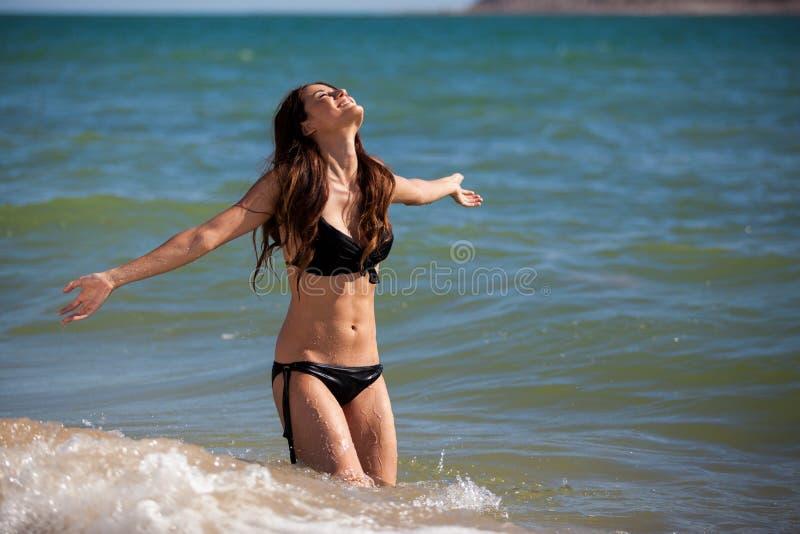Having fun in the water. Gorgeous young woman in a black bikini having fun in the ocean royalty free stock image
