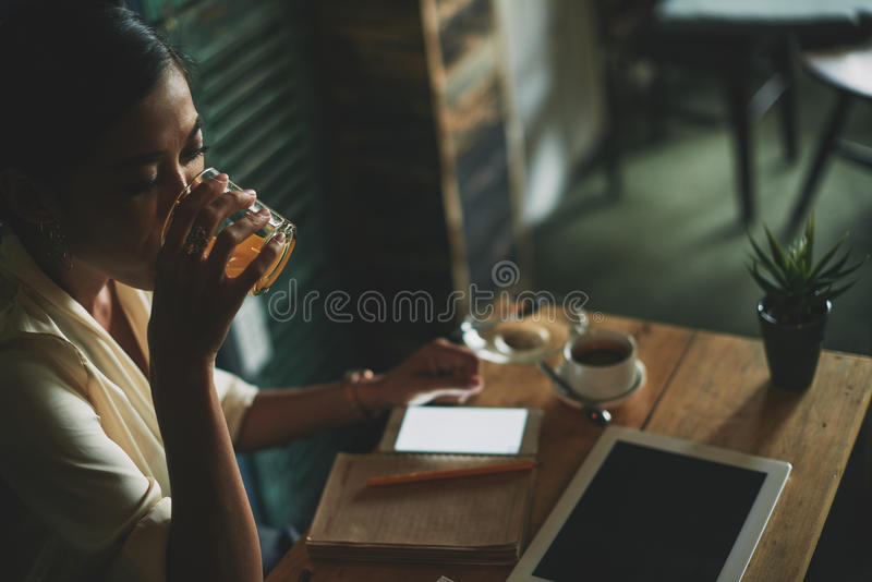 Having glass of fresh juice. Business lady drinking fresh juice in cafe before starting to work royalty free stock image
