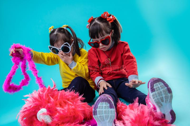 Stylish adorable girls with down syndrome playing with decoration. Having holiday mood. Stylish adorable girls with down syndrome playing with decoration for stock photo