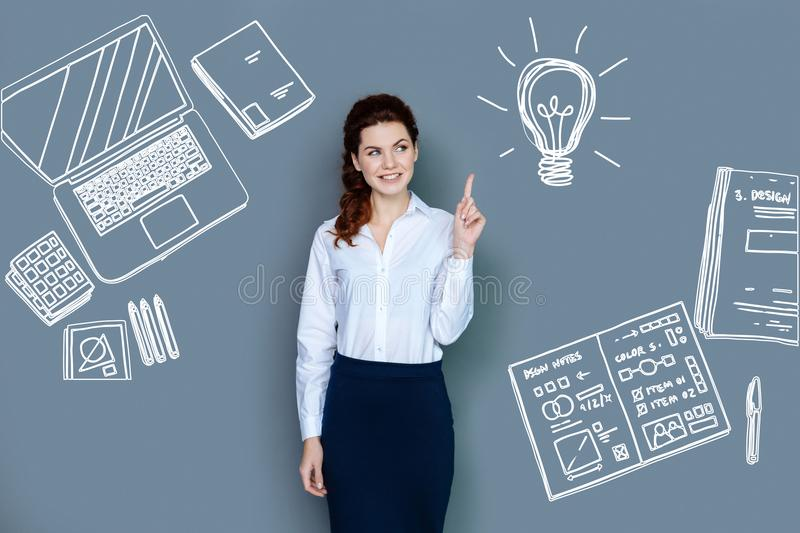 Creative web developer smiling while getting a nice idea. Having an idea. Positive young web developer feeling glad while getting a wonderful idea stock image