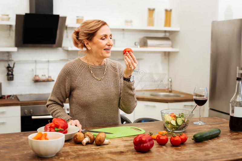 Positive woman with tied hair observing tomato in her hand royalty free stock photo