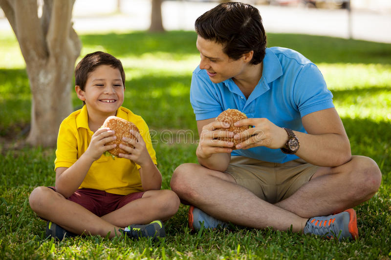 Having lunch with my dad. Cute happy boy spending some time with his dad and eating a hamburger in a park royalty free stock images