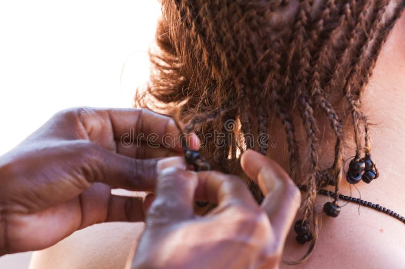 Having my cornrows done locally in Malawi stock images