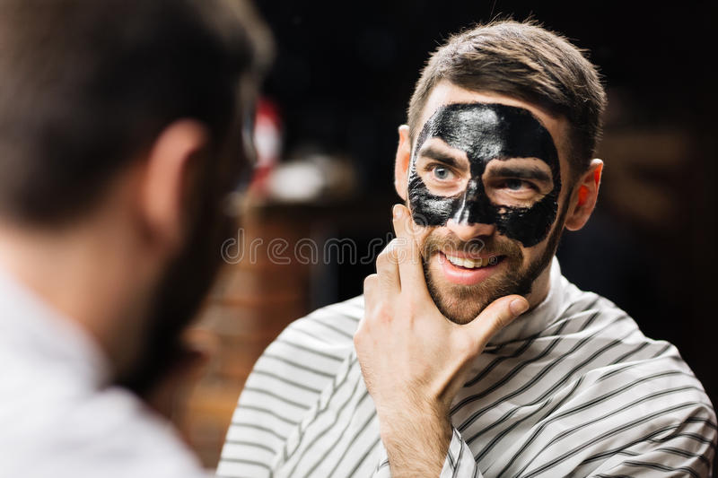 Having peel-off mask. Mirror reflection of handsome man with peel-off mask on face royalty free stock photo