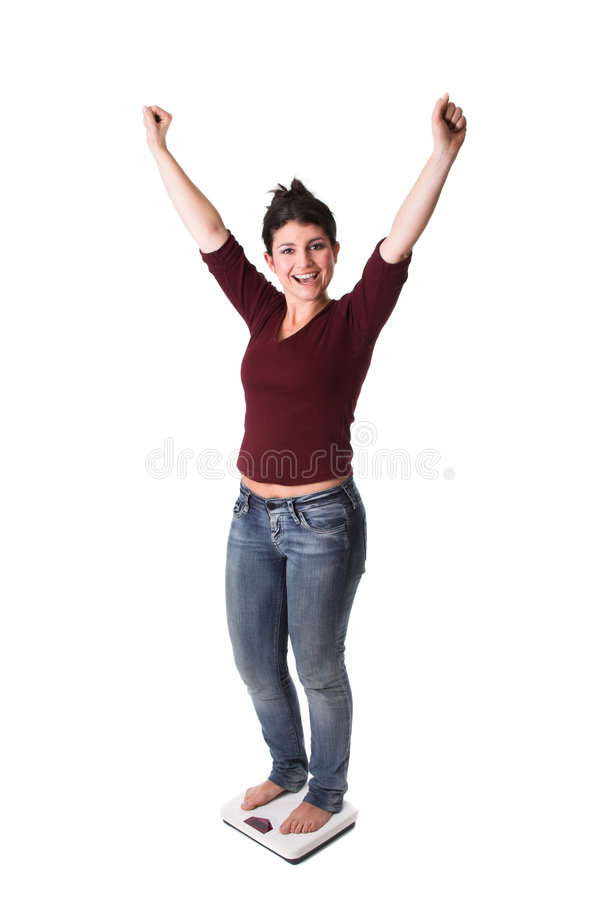 Having reached the target. Pretty brunette looking very excited while standing on the weighing scale royalty free stock images