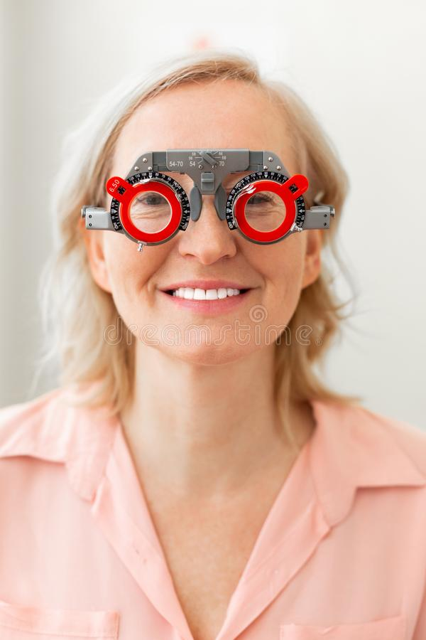 Beaming good-looking woman checking abilities of her vision with different lenses. Having special construction. Beaming good-looking woman checking abilities of stock photo