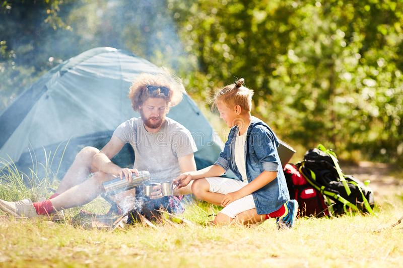 Having tea by campfire. Contemporary young scouts having hot tea while sitting on grass by smoking campfire on summer day royalty free stock photography