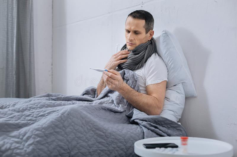 Sick male person looking at thermometer. Having temperature. Upset man covering his neck with scarf and wrinkling forehead, sitting under blanket on his bed stock photography