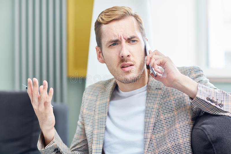 Having Tense Telephone Conversation. Annoyed young entrepreneur gesticulating and looking away with concentration while having tense telephone conversation with royalty free stock images
