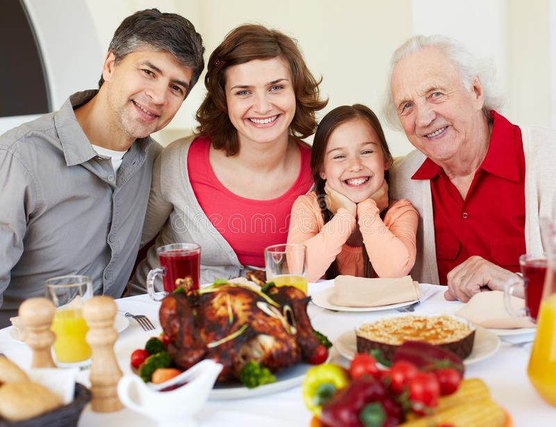 Having Thanksgiving dinner. Happy family sitting at celebration table on Thanksgiving Day royalty free stock images