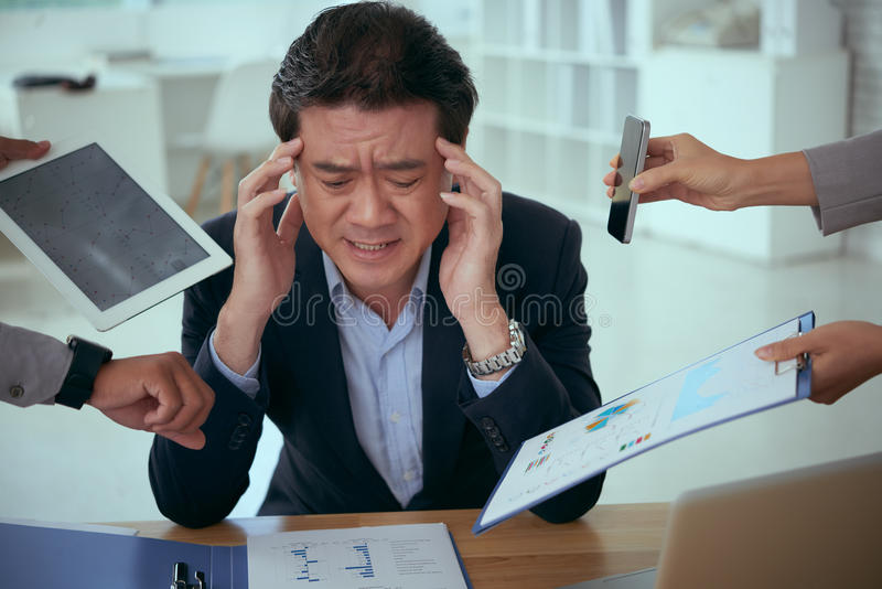 Having too much things to do. Tired unhappy businessman having many things to do stock photo