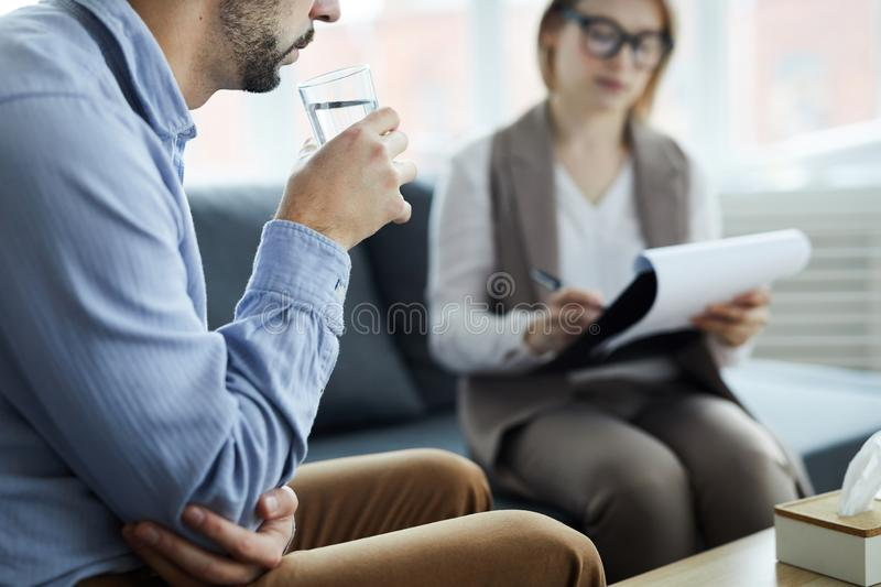 Having water. Troubled patient of counselor having glass of water while discussing his problems during psychological session royalty free stock image