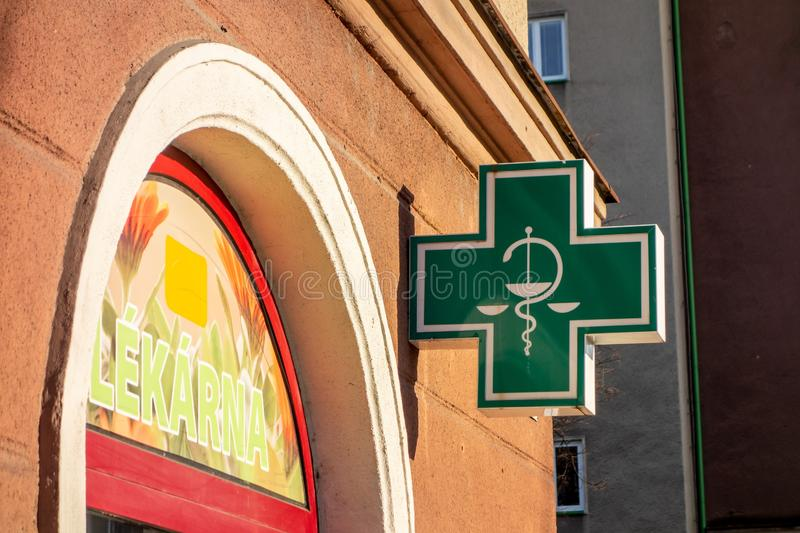 The typical green sign for pharmacies, drugstores and healtcare related shops in Czechia at sunset with Lekarna pharmacy ain royalty free stock image