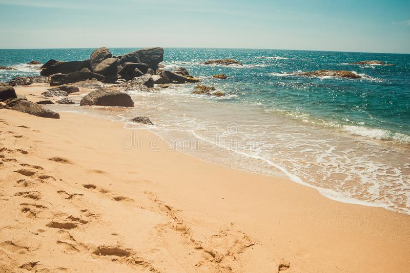 Havkust med stenar och kolsyrat vattenyttersida Tropisk semester feriebakgrund Öde fotspårstrand ParadisID arkivbilder