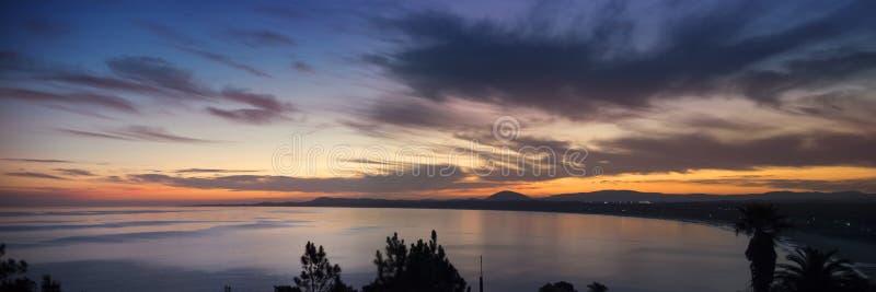Havkustpanorama med vatten och solnedgånghimmel arkivbild