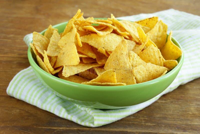 Havrechiper (nachos) i en grön bunke arkivfoto