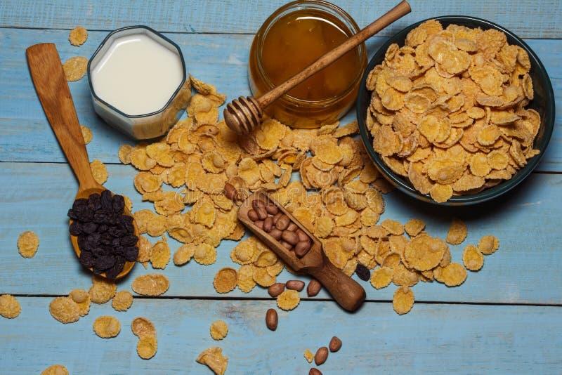 Havreflingor i en bunke på en trätabell med mjölkar och honung På en blå blå bakgrund sund frukostmat Selektivt fokusera royaltyfria foton