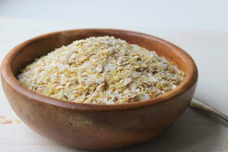 Havreflingor i en träbunke isoleras på en trätabell Sund mat, vegetarianism, sund livsstil, bantar royaltyfria foton
