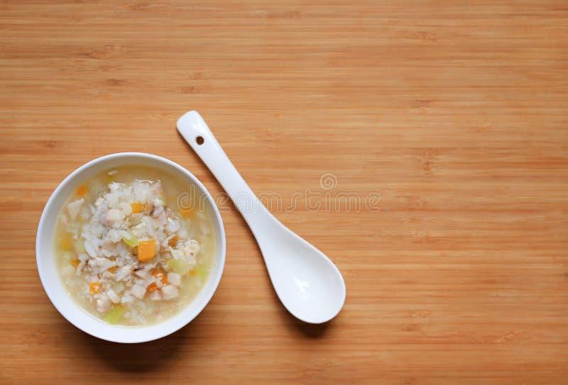 Havregröt för behandla som ett barn mat i den vita keramiska bunken och skeden med kopieringsutrymme på träbrädebakgrund royaltyfria foton