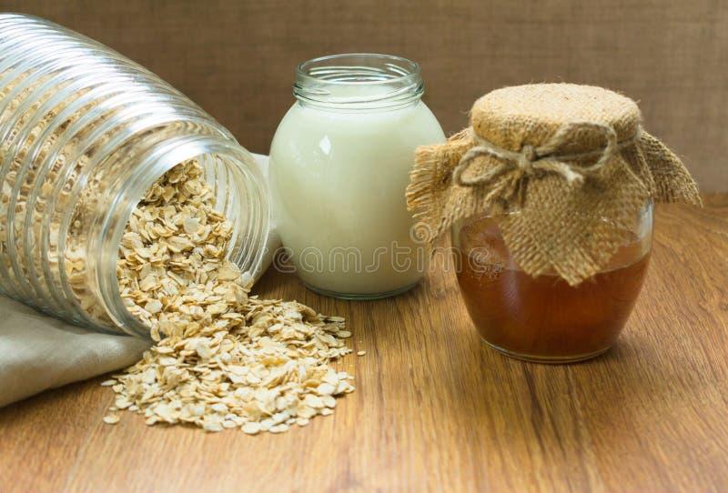 Havremjöl honung och att mjölka på tabellen Anv?ndbar frukost arkivbild