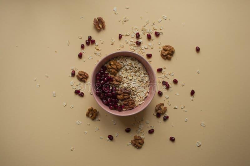 Havremjöl i en bunke med valnötter och granatäpplefrö omkring arkivfoto