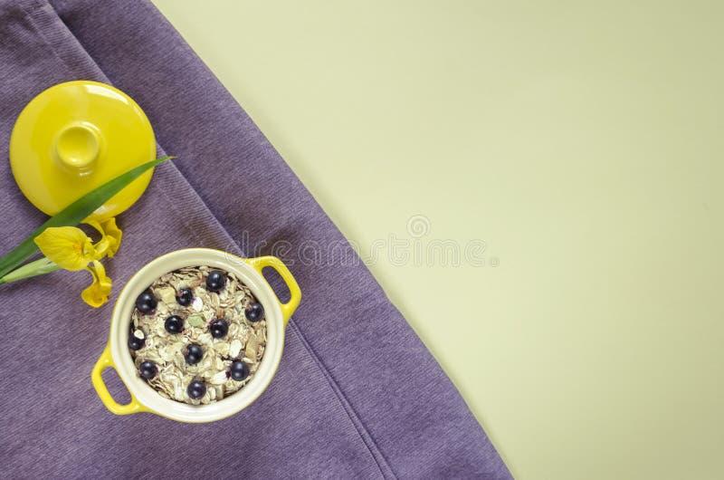 Havremjöl i en kruka, mysli med nya blåbär och vinbär Gul svärdslilja för garnering på en lila royaltyfri bild