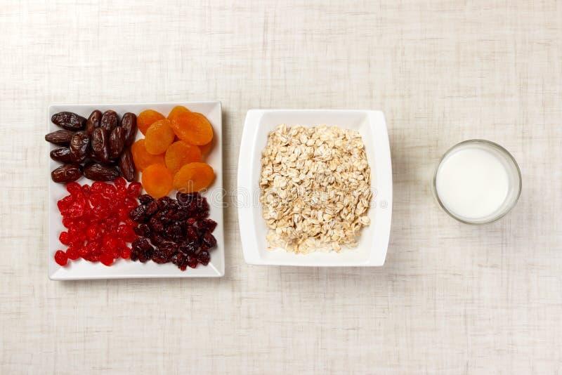 Havremjölet med mjölkar och torkade - frukt Användbar och sund frukostljusbakgrund arkivbild