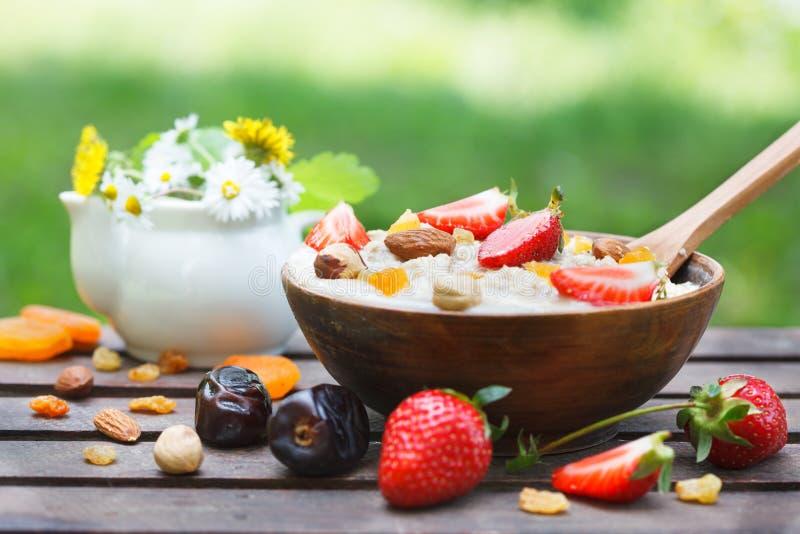Havremjölhavregröt i träbunke med nya jordgubbar, blandningmuttrar och torkat - frukt royaltyfri fotografi
