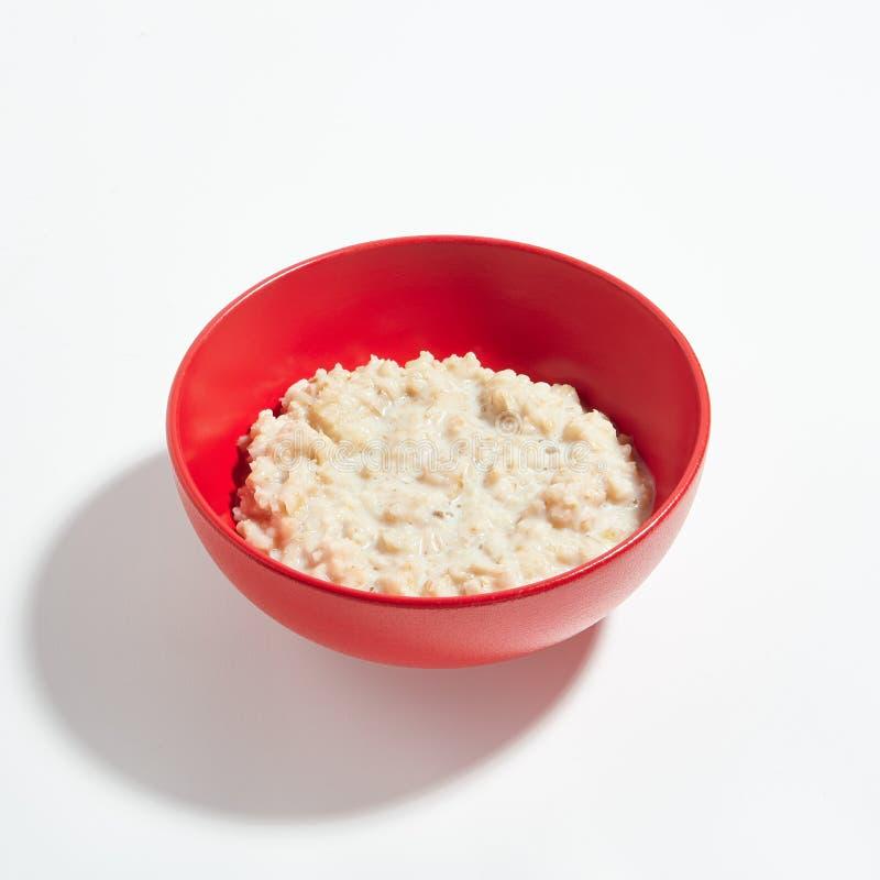 Havremjölhavregröt med mjölkar i den röda bunken som isoleras på vita Backgro royaltyfri foto