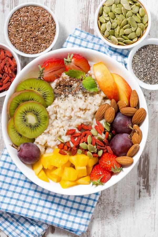 Havremjölhavregröt med ny frukt och superfoods för den sunda frukosten, vertikal closeup royaltyfri bild