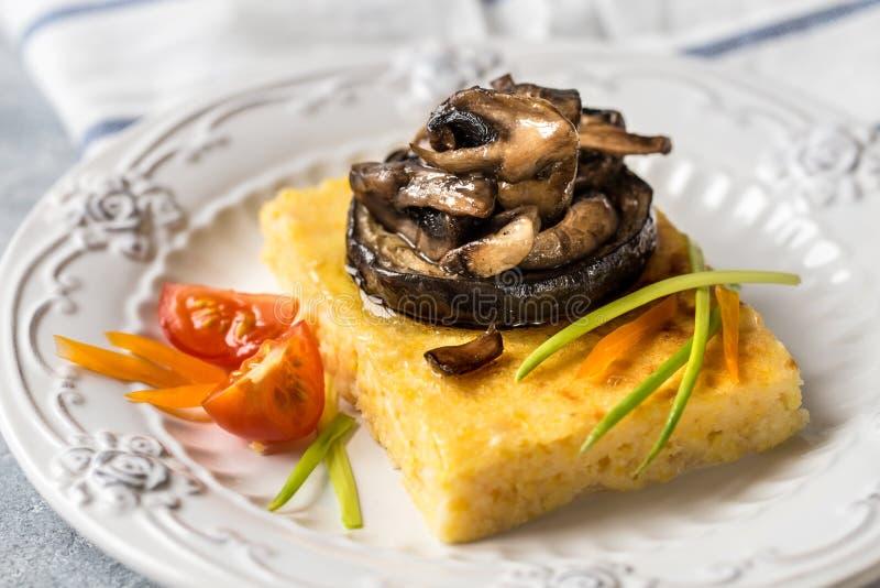 Havrepolenta med grillad champinjoner och aubergine, traditionell italiensk mat royaltyfria bilder