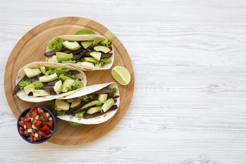 Havretortillor med den grillad nötkött, avokadot, limefrukt och salsa på träbräde Top beskådar royaltyfri foto