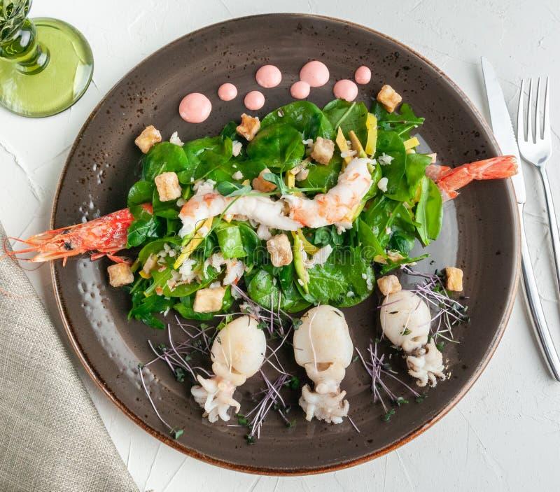 Havs- sallad Langoustino räka, tigerräka, bläckfisk, mango, avokado, arugula och spenat med grillad aubergine Leraplatta arkivbild