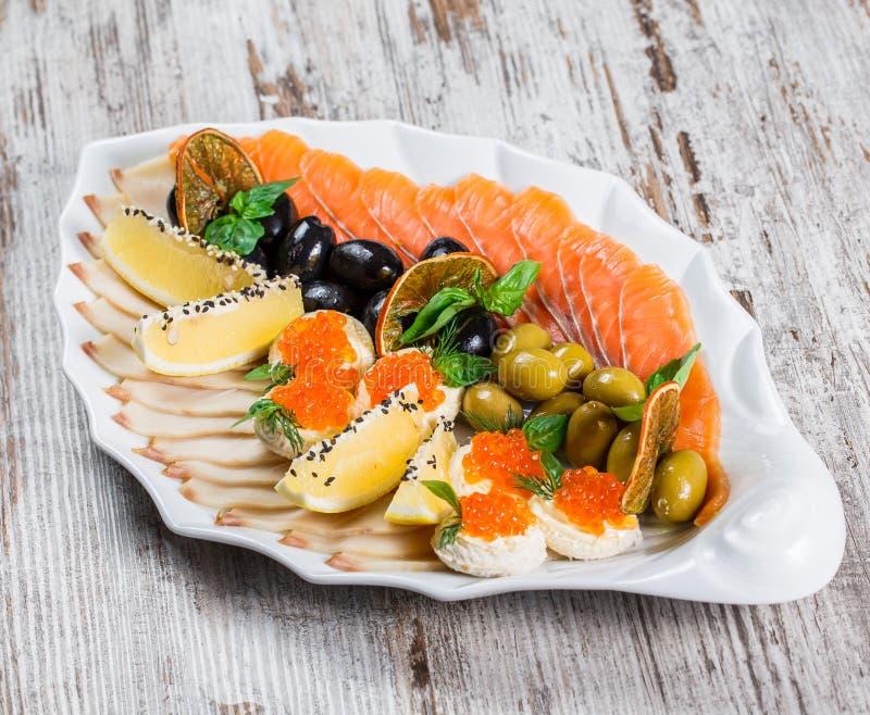 Havs- uppl?ggningsfat med laxskivan, vaktel?gg med den r?da kaviaren, skivafiskfil? som dekoreras med oliv och citronen i platta arkivbilder
